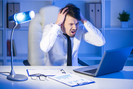 Young businessman shuts his ears with his hands while is working with laptop in his office.