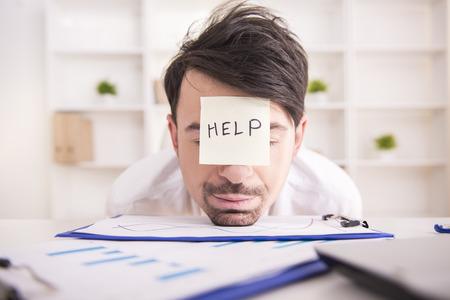 durmiendo: Joven hombre de negocios frustrados en su office.He necesita ayuda. Foto de archivo