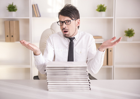 Busy businessman spectacled with a lots of folders photo