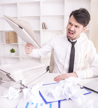 Angry businessman working in office and holding a paper photo