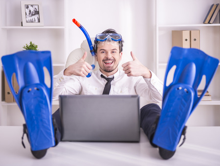 Happy businessman is working in office is wearing in fins. photo