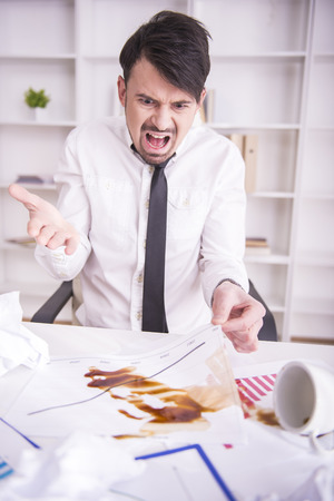 disarray: Businessman angry over spilled coffee on documents