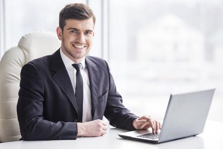 typing: Apuesto hombre de negocios est� trabajando con el ordenador port�til en la oficina est� mirando a la c�mara. Foto de archivo