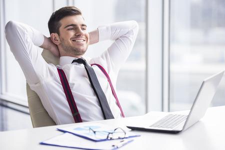 휴식을위한 시간. 젊은, 행복 사업가 그의 사무실에서 편안한입니다.