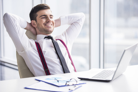 his: A time for relax. Young, happy businessman is relaxing in his office. Stock Photo