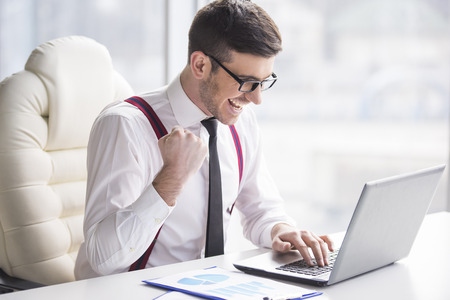 typing man: Young, happy businessman is working in his office. Stock Photo