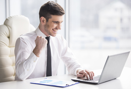 Jonge, gelukkige zakenman werkt in zijn kantoor. Stockfoto