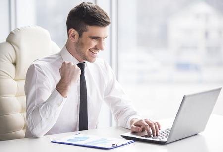 Young, happy businessman is working in his office. Foto de archivo