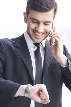 Businessman is looking at his watch while taking a call. photo