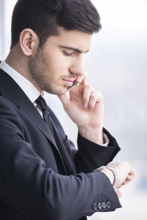 Businessman is looking at his watch while taking a call. Side view of. photo