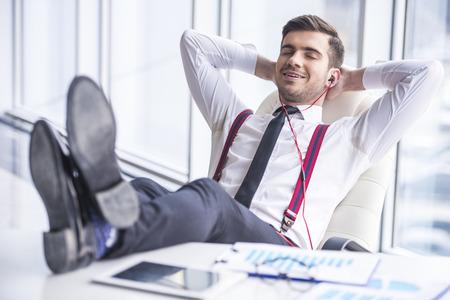 スーツは、オフィスでヘッドフォンで音楽を聴く若い男。 写真素材