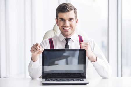 Young man in a suit holding a laptop in front photo