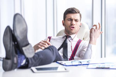 Jonge man in pak is het luisteren muziek in hoofdtelefoon op kantoor.