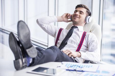 relajado: Hombre joven y sonriente en traje está escuchando música en los auriculares en la oficina. Foto de archivo