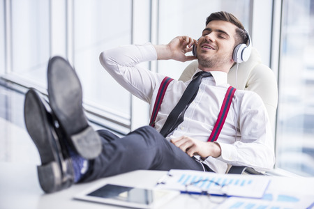 headphones: Smiling young man in suit is listening music in headphone in office. Stock Photo