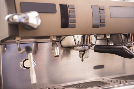capucinno: Barista prepares espresso in his coffee shop. Close-up