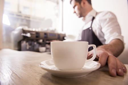 Barista prepares cappuccino in his coffee shop. Close-up cup of coffee.