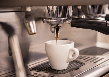 capacino: Close-up of an espresso machine making a cup of coffee.