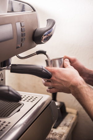 capacino: Hands of barista prepares espresso in his coffee shop. Stock Photo