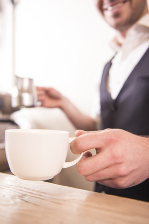 Handsome barista offering a cup of coffee to camera at the coffee shop. Blurred background.