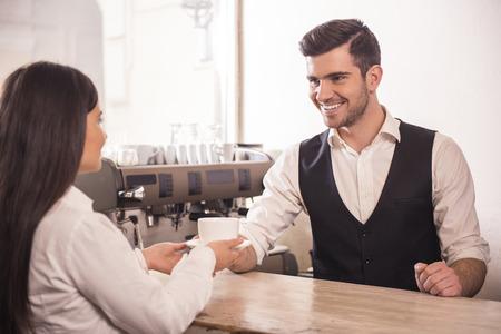 hombre tomando cafe: Barista dando taza de caf� para la mujer en el mostrador de la tienda de caf�.
