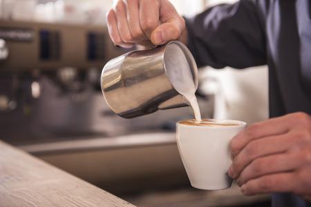 capuchino: Manos Barista está vertiendo la toma de leche cappuccino. Foto de archivo