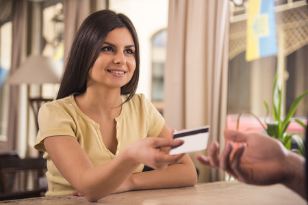 Smiling woman is paying for coffee by credit card. photo