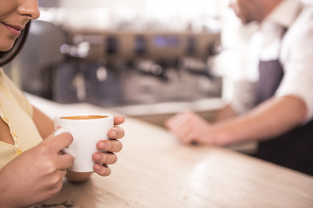 Smiling young woman is drinking coffee on a background coffee machine. Blurred background. Stock Photo