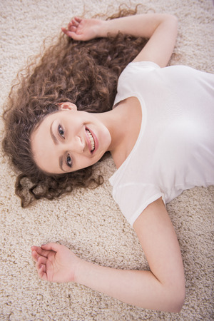 upper floor: Upper view of. Smiling woman is relaxing laid on floor. Looking at camera. Close-up. Stock Photo