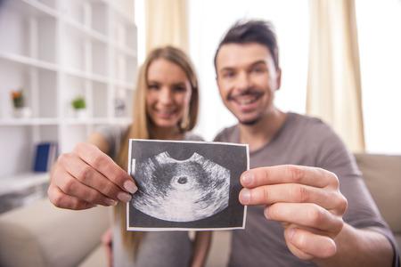 행복한 부부는 아기의 초음파 검사를 들고 있습니다. 스톡 콘텐츠
