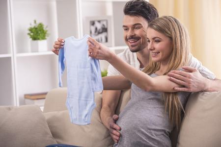 marido y mujer: Hermosa mujer embarazada con su marido son la celebración de los mamelucos en la ropa de las habitaciones de los niños.