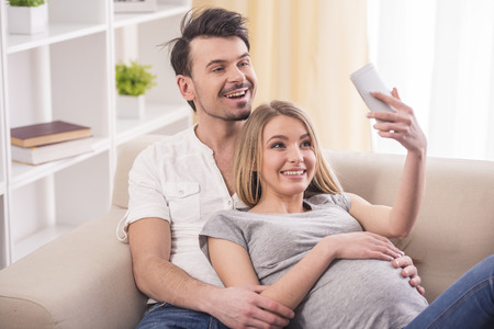pregnant woman with husband: A pregnant woman and her husband are photographing themselves on the cell phone at home. Stock Photo