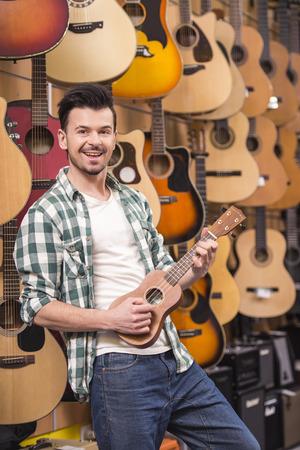 ukelele: Man is playing ukelele in music shop. Stock Photo