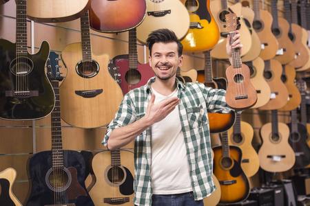 ukelele: Man is holding ukelele in music shop.