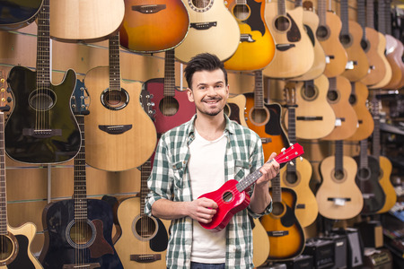 ukelele: Man is holding red ukelele in music shop.