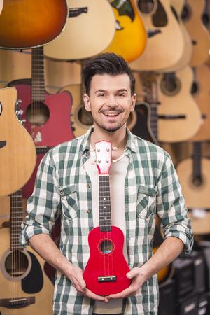 ukelele: Smiling man is holding red ukelele in music shop.