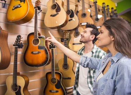 Man and woman are considering a guitars in a music store. photo