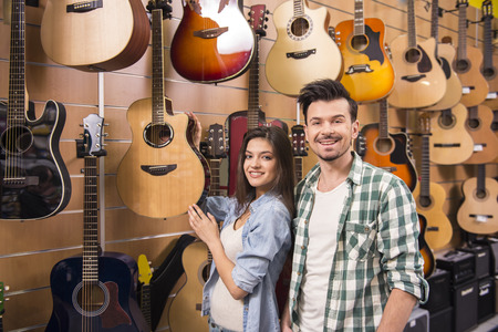 Young man and girl are smiling on the background of guitars in the music store. photo