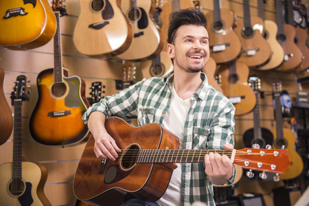 Man is playing on guitar in music shop. Stock Photo