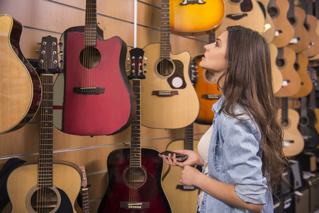 Beautiful young girl is chooses a guitar in music store. photo