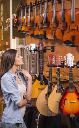 Young girl is choosing violin in a music store.