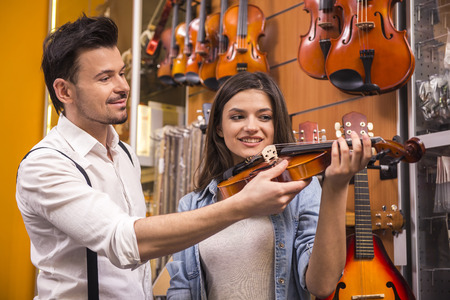 teaching music: Young man is teaching girl to play the violin at the music store. Stock Photo