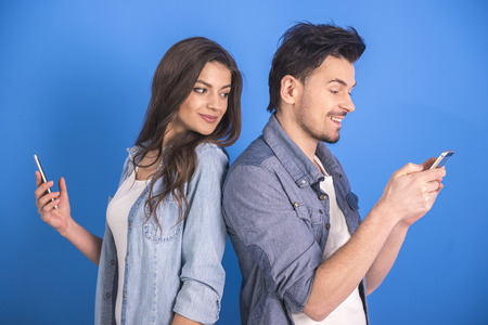 Attractive young couple are looking at smartphone on blue background.