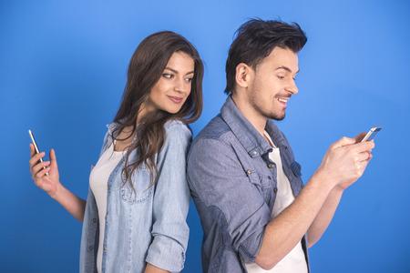 junge nackte frau: Attraktive junge Paar an Smartphone auf blauem Hintergrund sucht.