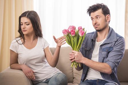 marido y mujer: Hombre joven ofrece un ramo de flores a su novia enojada en casa.