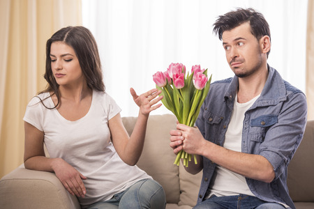 apologize: Young man is offering a bunch of flowers to his angry girlfriend at home. Stock Photo