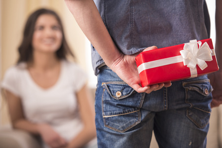 wife and husband: Guy is holding gift behind him is trying to surprise his is waiting girlfriend at home. Focus on boy. Stock Photo