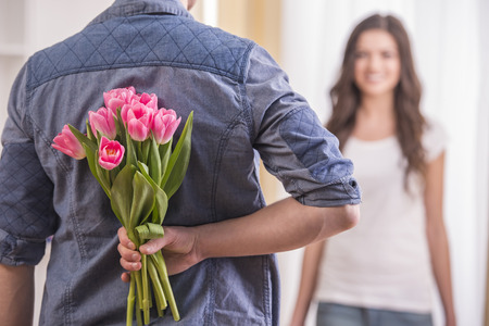 giving: The young man is hiding flowers behind their backs to his girlfriend at home. Stock Photo