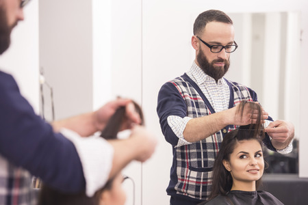 Handsome hairdresser making a haircut for a beautiful brunette girl. photo