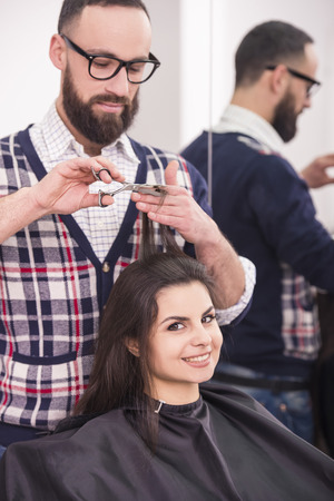 hairdressing scissors: Handsome hairdresser making a haircut for smiling  client in in hairdresser salon. Stock Photo